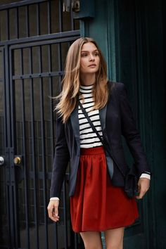 Model Josephine Skriver wears fitted blazer, striped tee and pleated miniskirt