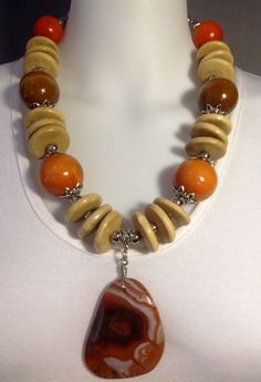 Bold statement necklace in shades of fall. Polished agate pendant, wooden discs and large beads wire wrapped on belcher chain. Brown, orange, cream - Michela Rae