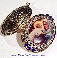 $124 Large vintage gold plated reliquary locket pendant with a porcelain center cameo featuring the blessed mother virgin Mary and the child Jesus Christ. Gorgeous AB rhinestones surround and there are royal blue rhinestone accents. Inside are more blue rhinestones and a vintage colored Miraculous Medal featuring Our Lady of Grace on the right. The left can hold a photo or your prayer petition request.