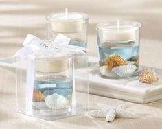 DIY beach wedding table centerpieces - Just fill a glass with blue water, put some shells on the bottom, and float a candle on top!