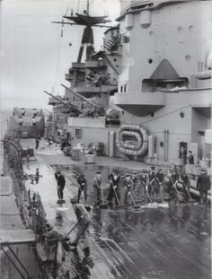 Crew of 16 in battleship HMS Rodney on fatigues whilst 'alongside'. Together with HMS King George V she accounted for the crippled Bismarck in May 1941.