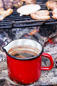 Red metal cup of coffee made near bbq in the wilderness