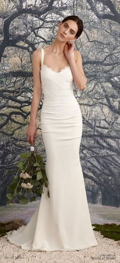 Mermaid cut gown center back and side ruching to slim and shape the figure. Faux-wrap v-neck bodice with scalloped lace detail. Classic shoulder straps lead into a deep v-back and fishtail train.