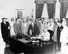 President Truman signs the National Security Act Amendment of 1949 in the Oval Office.