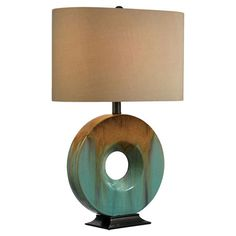 Cast a warm glow in your home office or den with this eye-catching ceramic table lamp, showcasing a ring-shaped base and fabric shade.  ...