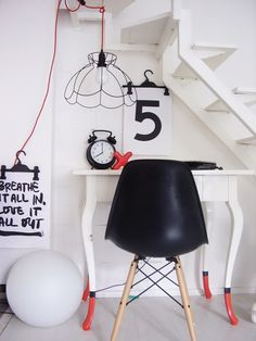 White office space with wire lamp shade, red cord