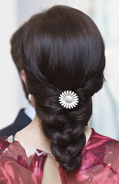 A white enemal and diamond brooch in the hair: