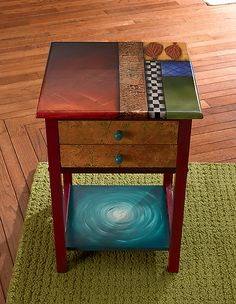 Cute hand painted wooden table w/2 drawers and a bottom shelf. Warm reds and ambers.... Gotta have it!