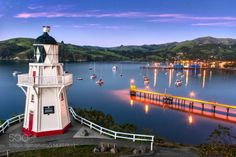 Akaroa Lighthouse at dusk. Akaroa New Zealand by dreamscapenz  landscape sunrise sunset water reflection travel blue harbour lighthouse new zealand boats evening y