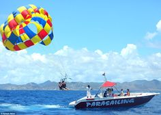 Fun in the sun: Khloe and Kylie laughed and held their feet high in the air as they tried to avoid getting wet as the parasail dropped down from the sky