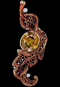 PENDANT  1 oval sphene 24,39 ct  25 diamonds 0,47 ct  142 cognac diamonds 0,89 ct  32 red diamonds 0,20 ct  108 orange diamonds 0,66 ct  32 green diamonds 0,14 ct  18K yellow gold 17,9 g