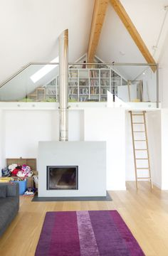 Contemporary family home designed by Cornwall architects The Bazeley Partnership.  Log burner supplied by Kernow Fires. #logburner #fireplace #newbuild #familyhome #selfbuild #mezzanine #livingroom #contemporary #modern #glazedbalustrade
