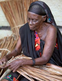 Swahili Woman makes coconut palm thatch used as roofing material .  Lamu Island . Kenya