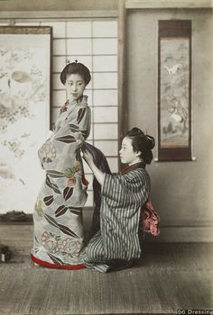 """""""Two young women wearing traditional Japanese garments; kneeling woman at right wearing blue and grey striped kimono assists standing woman at left, wearing a flowered kimono with blue ground, with tying her obi; folding screen and hanging scroll in background.""""  About 1900, Japan.  Text and image via MIA"""