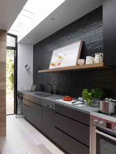 Sanders & King St Kilda 38 | Est Magazine Kitchen cupboard fronts | LAMINEX black and 'Burnished wood' laminates Kitchen Benchtop | STONE ITALIANA 'Jaipur' colour Thyme Kitchen Tiles to splash back | ONSITE Obsis matt black tiles