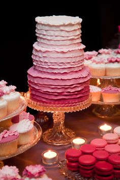Simple use of a clear tealight candle holder with a tealight candle to add just a bit of glow.  Lovely dessert table. Cake, macaroons and cupcakes all sporting the ombre theme. LOVE IT!