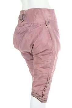Rear view, pair of breeches, late 18th century. Lilac silk taffeta with silver thread embroidered knee buttons and band.