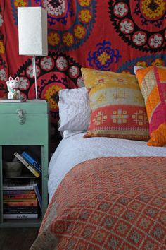 Dallas, TX: Paige Morse eclectic bedroom--orange/red textiles, white sheets, light green side table.