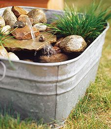 Build a mini water garden oasis - I really love the choice of a washtub for this, would be really nice for a #rustic setting, or a simple #farmhouse #porch info for building, including tips, plant suggestions, etc. By Christina Selby - #water #garden #DIY #mini #pond #washtub #rocks #waterfall #pump #deck #patio - tå√