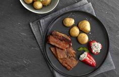 Gelakt varkensbuikspek met gebakken krieltjes en gevulde puntpaprika's