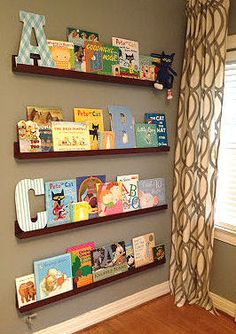 Floating shelves in a baby nursery take the place of a free standing bookshelf