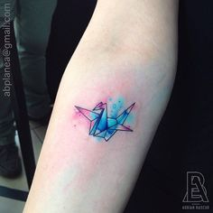 Forearm tattoo of an origami crane with a watercolor background. Tattoo artist: Adrian Bascur