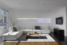 Modern living room space, minimal wall decor, large open windows with white sofa.