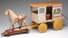 """""""BORDEN'S FARM PRODUCTS"""" WOODEN DELIVERY WAGON,  with painted, stenciled and applied lithographed decorations, original wooden milk crate and 11 bottles, along with a German-made horse on platform pull toy."""