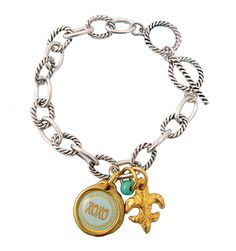 Don't worry about mixing silver and gold with this two-toned bracelet that helps tie your favorite gold & silver jewelry together. A classic look with an updated twist. Layer it with one of our Good Energy bracelets. Toggle bracelet is adjustable; charms are hand poured pewter, Fleur de lis & XOXO charm with glass Czech bead accent. Made in USA.