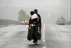 Superman - dad.  Idomeni. A Syrian refugee kisses his daughter as he walks through a rainstorm towards Greece's border with Macedonia, in September.  Guardian photographer of the year 2015: Yannis Behrakis