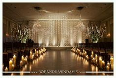 Gladiolas suspended from the  ceilings with chandeliers and crystals. Candle lined asile way.