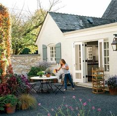 outdoor alfresco design backyard patio gravel pebble floor french country style table and chairs lavender window shutters