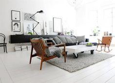 Woonkamer in wit en grijs. In de woonkamer van dit appartement speelt contrast een hoofdrol. De zwarte bank en witte gietvloer vormen de basis.