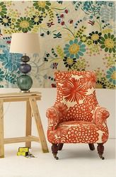 the chair! the lamp!...living room with wainscoting. patterned chair in orange and floral. simple sidetable. glass lamp. funky blue/green wallpaper with retro floral pattern.