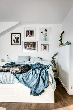 Plan deschis, cărămidă expusă, grinzi de lemn și un colț de relaxare la înălțime în această mansardă spațioasă din Suedia.