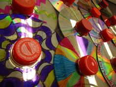 DIY spinning tops from a CD, bottle cap, and marble. AWESOME!!