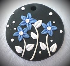 Polymer clay pendant, handmade with applique technique, one of a kind.Black with sparkly blue flowers, white stems, leaves and dots. By Lis Shteindel.