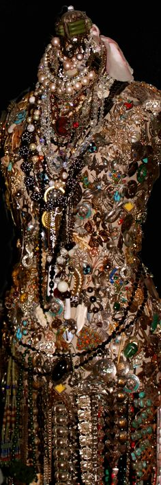 vintage collection of jewelry completely covering a dress form