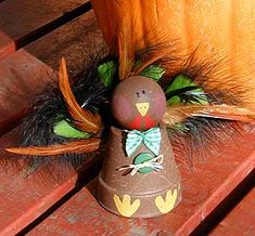 We made these as Brownies.  WE used raffia instead of bow ties.  Thank goodness, I had lots of parent help.  The girls needed help.  I think I would use hot glue for feathers and google eyes instead of painting on.  We cut the beak and feet out of felt and glued on.  Thanksgiving Crafts: Clay Pot Turkey