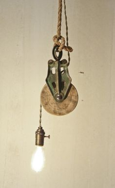 Another cool idea of how to rework everyday objects into stunning functional devices.  Barn pulley with rayon cord bare bulb hanging light.  Neat! #business ideas