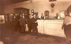 Patrons of a Pearl Street Bar - Photo taken by Joseph Sturtevant, showing the patrons of a local Boulder Pearl Street bar located in the 1100 block of Pearl St. Standing behind the bar right to left is Joe Durr and Louie Garbarino. 1104 Pearl Street. (1895) REPRODUCTIONS