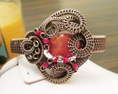 This cuff features a stunning hot pink oval Agate bead and is accented with red Swarovski Crystals. Oxidized copper swirls and surrounds the center. This cuff c