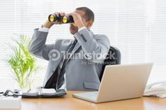 Stock Photo : Businessman looking through binoculars at desk