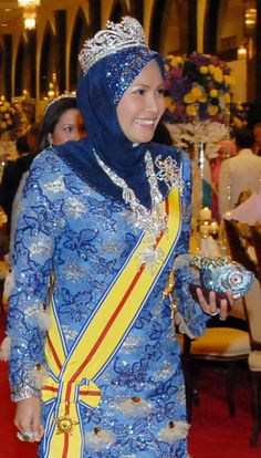 """Queen Nur Zahirah of Malaysia wearing the Gandik Diraja Tiara. Crafted from platinum and diamonds, it incorporates several traditional motifs: a central star with a crescent and the swiriling """"awan larat"""" design. The current version was remounted from a previous diadem by Garrard in 1984 and is designed to break down into a locket and set of brooches."""