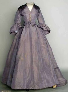 "LILAC SILK DAY DRESS, EARLY 1860s 2-piece faille, peplum bodice, trained skirt, B 36"", W 21.5"", L 41""-57"", (light skirt stains, water stains on peplum, alterations, sleeve flounce basted on) very good."