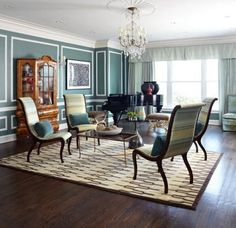 """Colourful Living Rooms:  Cool colours make a striking impact in this spacious living room.  Walls are dressed in peacock-blue, with simple white trim.  A sitting area, established by a geometric area rug, features a quartet of chairs covered in """"New Wave"""" fabric from Old World Weavers.  Gilt stools and a wooden cabinet invite small doses of warmth into the room.  Design: Melanie Elston, Photo: Werner Straube   Traditional Home"""