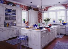 Red, white, and blue kitchen with china cabinet and trim moulding