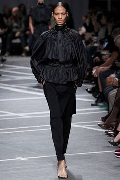 In the black color story of the runway show, this look features an airy silhouette with bishop-like sleeves and  a chin high neckline / #Givenchy #SS013