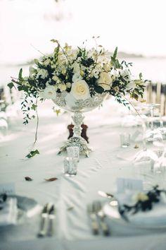 Ivory Flowers & Greenery in Metallic Goblet | Photography: Tom Moks Photography. Read More:  http://www.insideweddings.com/weddings/elegant-simple-destination-wedding-on-the-beach-in-mexico/864/
