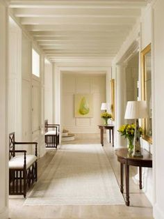This entry hallway by Phoebe Howard features clean & simple design with two dark wood benches with demilune tables on the opposite wall...V